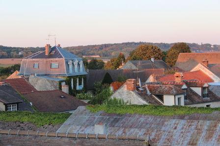 Vue des toits de Davron sous le soleil couchant